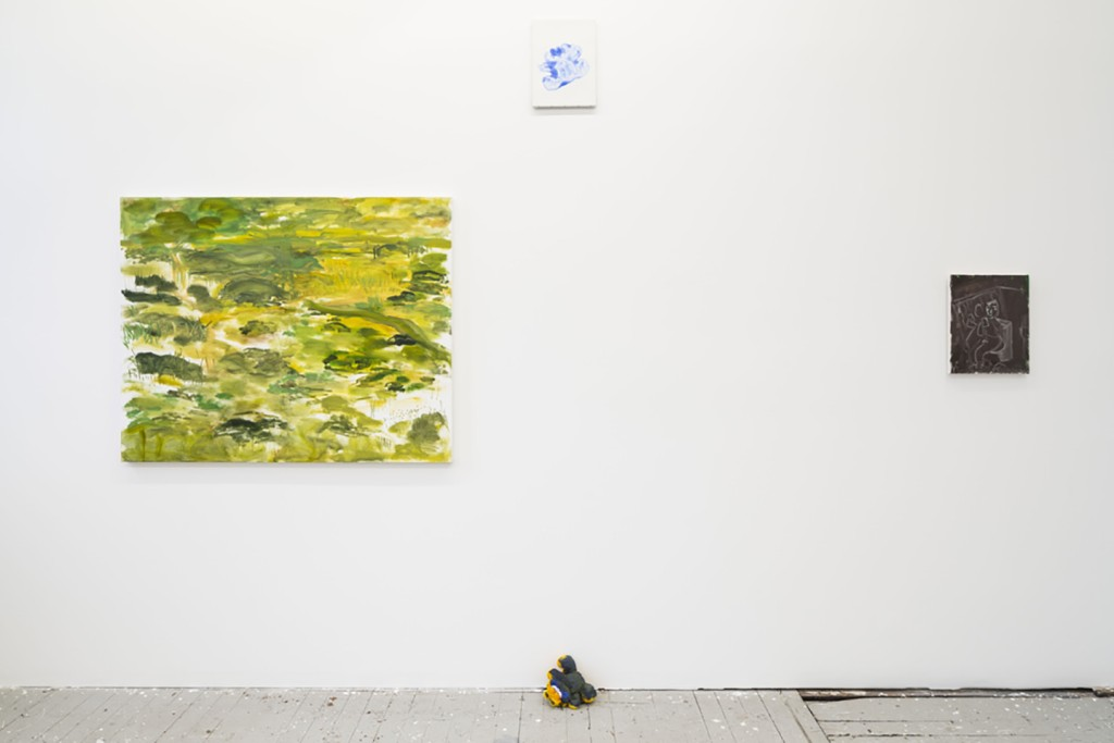 Installation view showing a green and yellow landscape painting and a dark brown painting with a teals ketch of someone sitting on the toilet. In between the two paintings, there's a Garfield doll covered in blue paint on the floor. Above him is a white canvas with a garfield-shaped blue imprint.